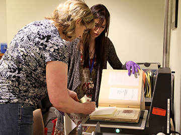 DHW employee Courtney Meek, left, works with archivist Layce Johnson to scan in the scrapbook in May at the Idaho State Archives.