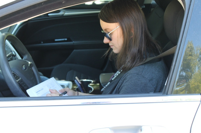 Clinician Ashley Hammond stops to take notes on her meetings while in her car