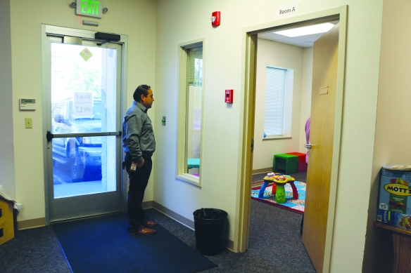 Carlos Ramos observes a parent and a child on a supervised visit.
