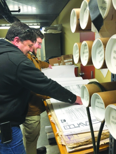 Danny Knobel, left, and Dan Asbury share a laugh as they review building blueprints.
